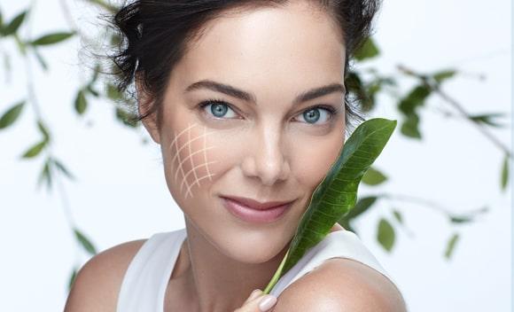 mujer usando crema facila bio resist con naturaleza, hojas a su alrededor, tecnologia innovadora